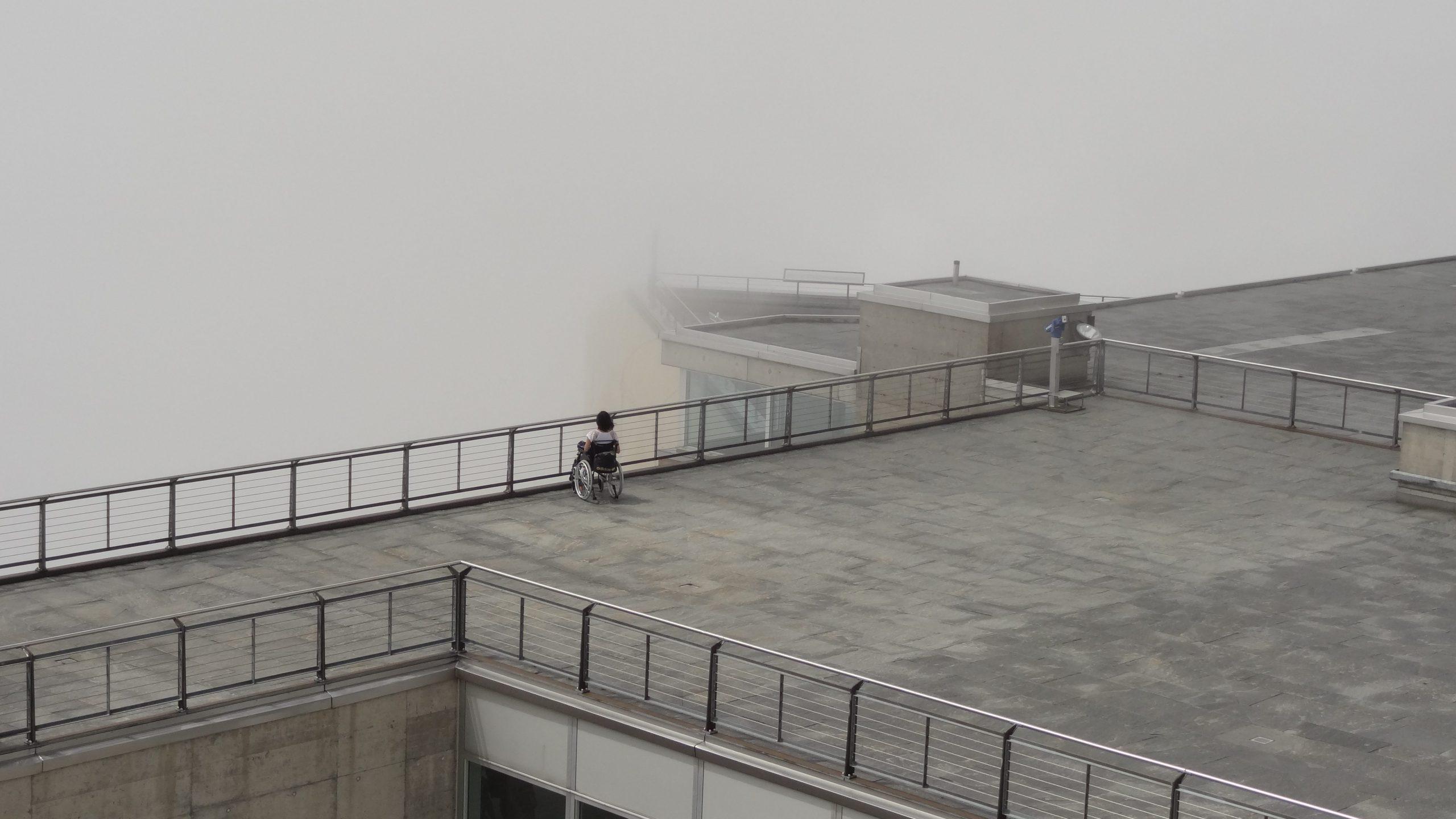 Simone sitzt im Rollstuhl vor einer riesigen Nebelwand
